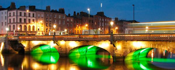 dublin by night showing green lights unders a bridge
